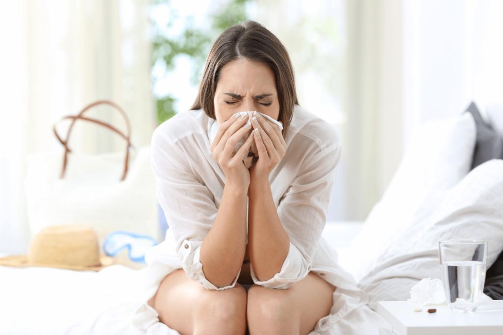 Kobieta siedzi na łóżku i kicha