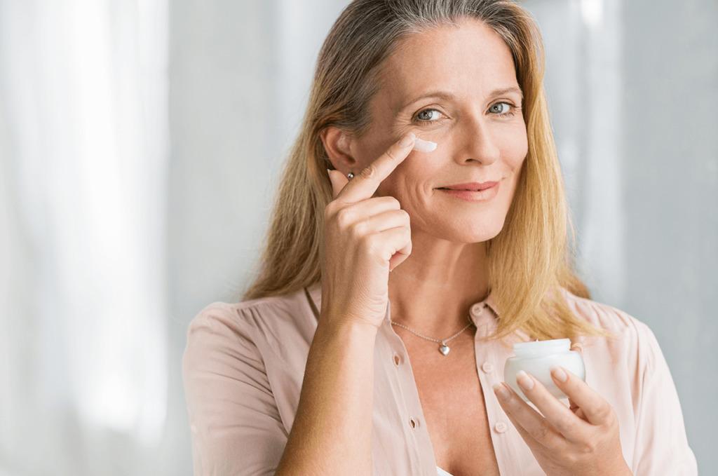 Kobieta nakłada krem na dojrzałą skórę