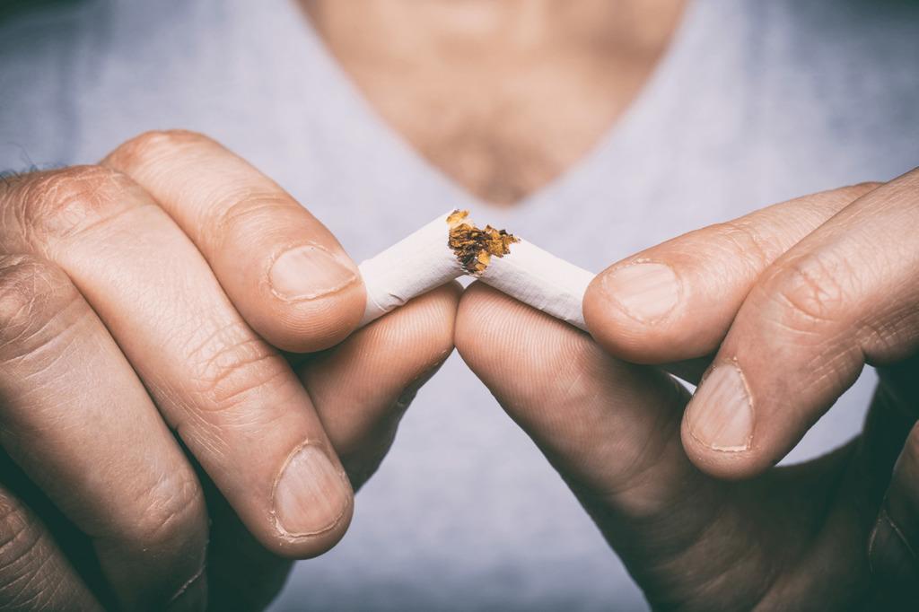 Mężczyzna, który łamie w dłoniach papierosa
